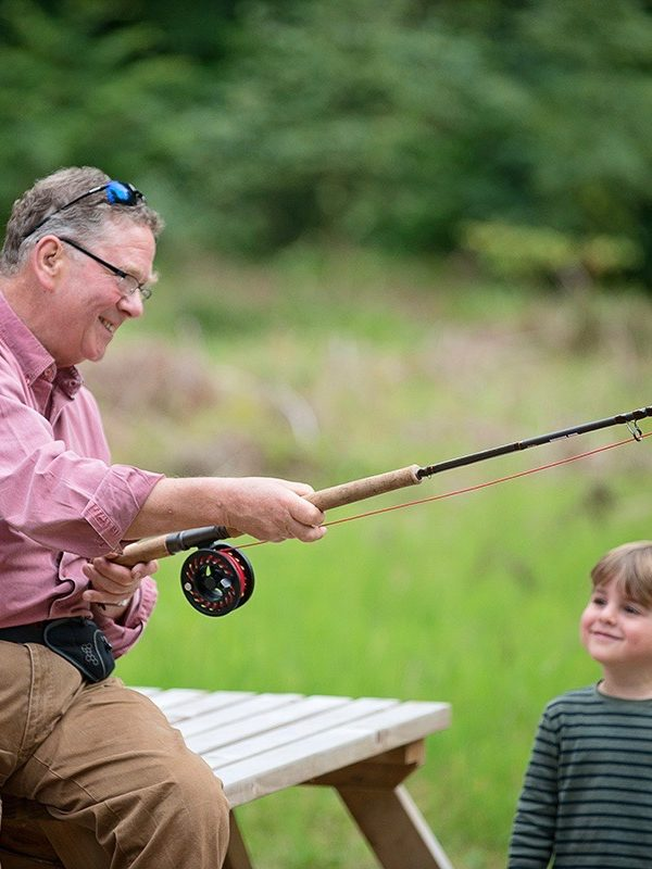 grandfather with grandson learning to fish