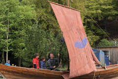 Henry Fosbrooke giving the kids a go at hoisting the sail in his wooden boat