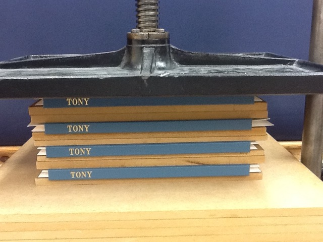 newly created books resting in the press - Laura West bookbinding course