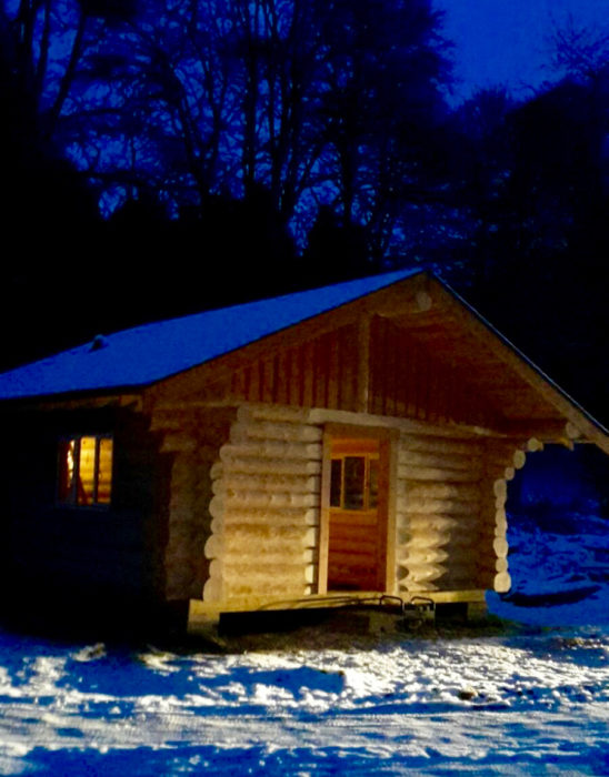 Canadian log cabin fishing hut at night . Nearly finished