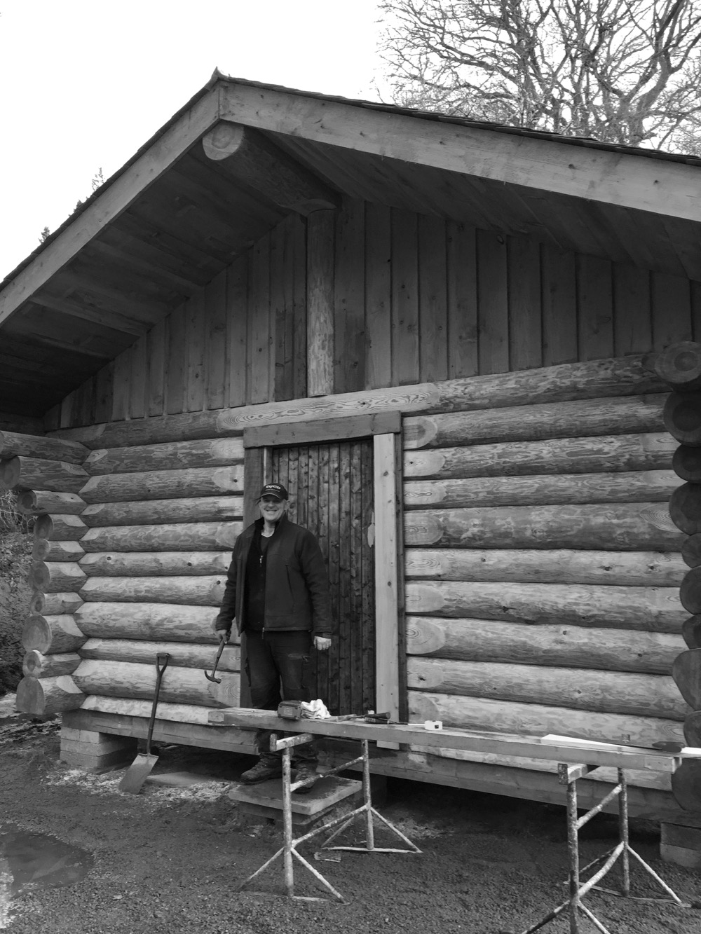 Ewen in front of the Canadian log cabin he built