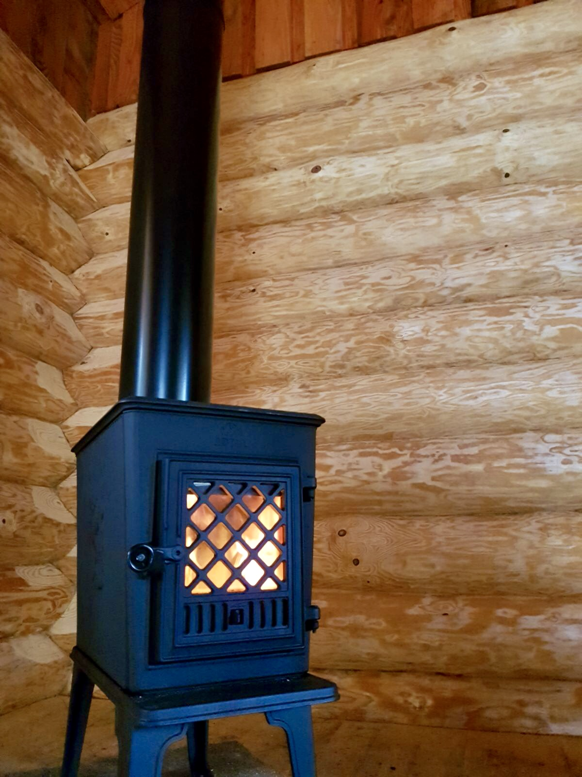 fishing hut log burner lit